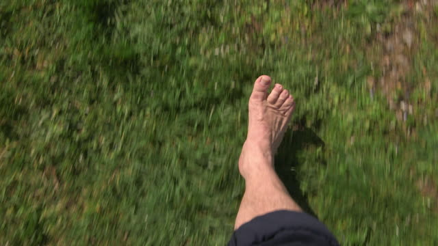man walking about meadow with bare feets, close of feets, from above - barefoot点の映像素材/bロール