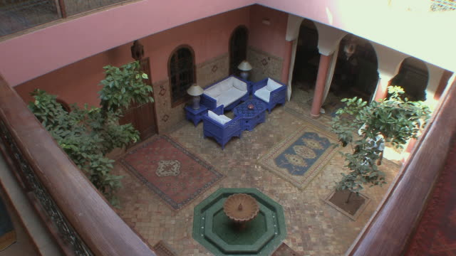ws ha man walking across courtyard in riad, marrakech, morocco - standing water stock videos & royalty-free footage