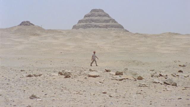 ws zo man walking across desert near step pyramid of zoser / saqqara, egypt - saqqara stock videos and b-roll footage
