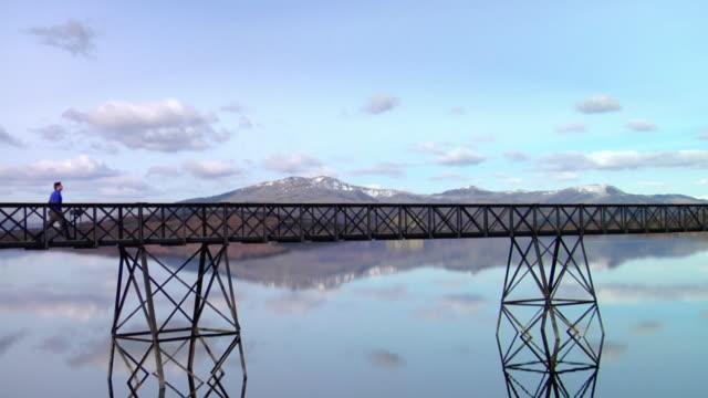 ws man walking across footbridge over lake / trawsfynydd, snowdonia, uk - wales stock videos & royalty-free footage