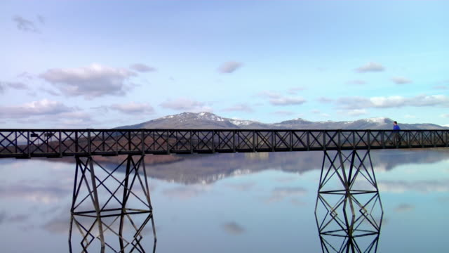 ws man walking across footbridge over lake / trawsfynydd, snowdonia, uk - snowdonia video stock e b–roll