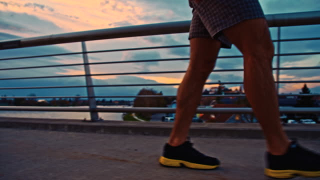 TS Man Walking Across The Bridge At Dusk