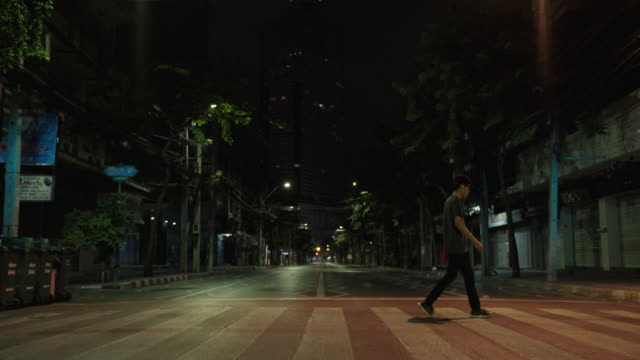 a man walking across the street - nightlife stock videos & royalty-free footage