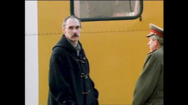 """vídeos de stock, filmes e b-roll de man walking alone on empty urban landscape; """"vb"""" truck entering through gate, group of riot police in the background; bald man with mustache looking... - ponte carlos"""