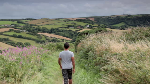 man walking along a foot path in devon - devon stock videos & royalty-free footage