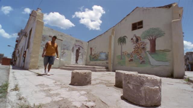 stockvideo's en b-roll-footage met ms, la, man walking along buildings with murals, havana, cuba  - baseballpet