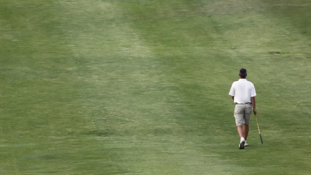 ws man walking along golf course / palma de mallorca, mallorca, baleares, spain - golfplatz green stock-videos und b-roll-filmmaterial