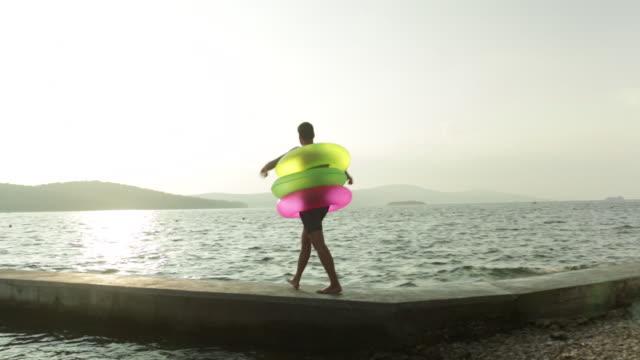 man walking along jetty wearing three inflatable rings. - ブラック島点の映像素材/bロール