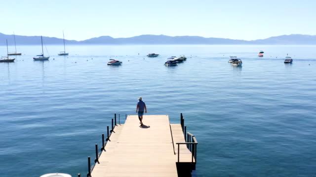 man walking along pier at lake tahoe - pier stock videos & royalty-free footage