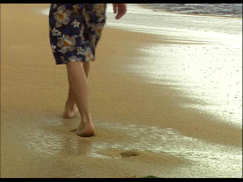 man walking along sandy beach, rear view, waist down - see other clips from this shoot 1158 stock videos and b-roll footage