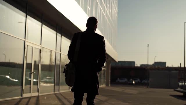 vídeos de stock, filmes e b-roll de homem andando ao longo do moderno edifício de negócios - vista traseira