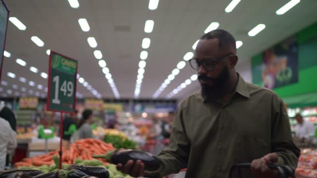 vídeos de stock, filmes e b-roll de homem andando e comprando em supermercado - orgânico