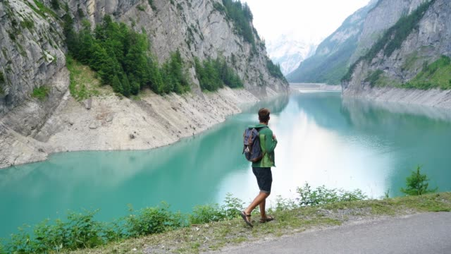 man walking and  looking at dam in swiss alps - hydroelectric power stock videos & royalty-free footage