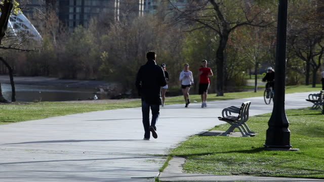 MS Man walking and three girls jogging on waterfront trail at Toronto / Toronto, Ontario, Canada