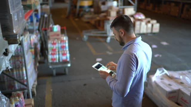 man walking and using digital tablet at warehouse - warehouse stock videos & royalty-free footage