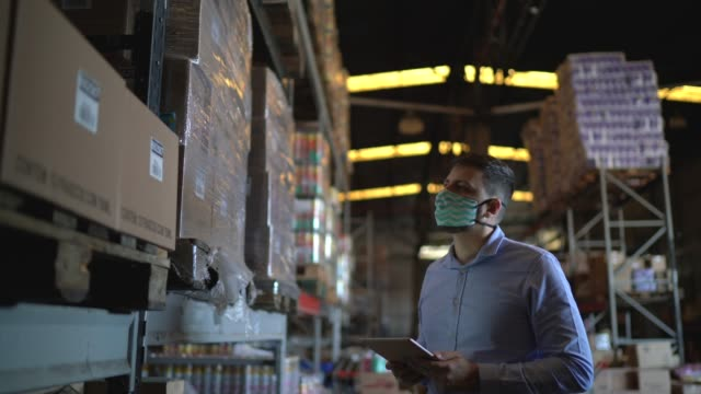 vídeos de stock e filmes b-roll de man walking and using digital tablet at warehouse - with face mask - trabalhador de armazém