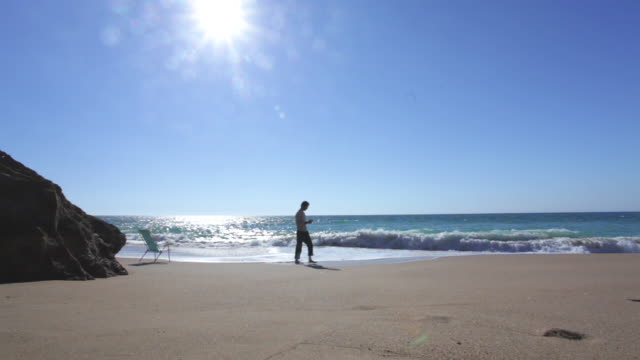 stockvideo's en b-roll-footage met man walking and using his phone in a delightful beach with nobody - silvestre