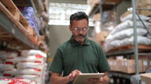 vídeos y material grabado en eventos de stock de hombre caminando y usando su tableta trabajando en almacén / industria - típico de la clase trabajadora