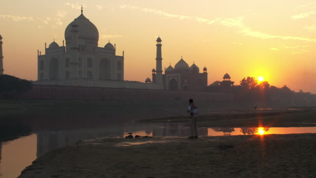 vidéos et rushes de man walking around as the sunsets behind the taj mahal. - inde