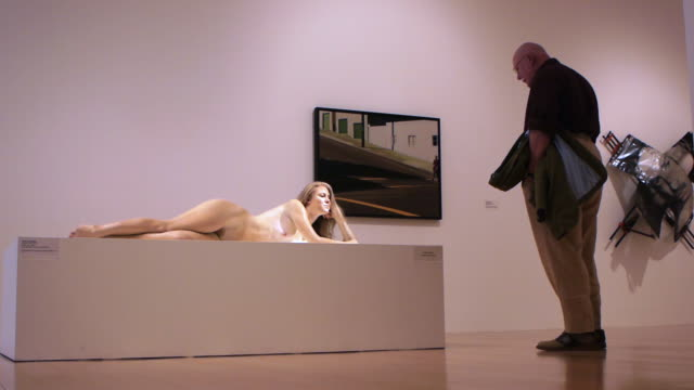 vídeos y material grabado en eventos de stock de ws man walking around full size hyper real sculpture of nude woman laying on wood pedestal at art museum / palm springs, california, usa - museo de arte