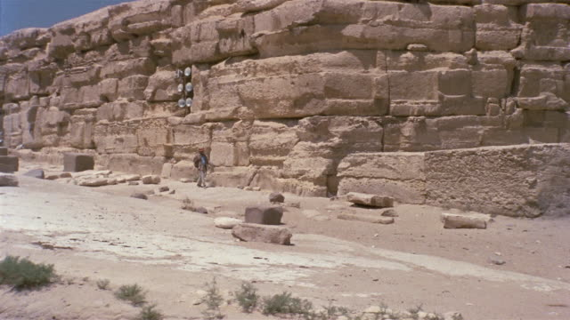 ws zi man walking around large stone wall and entering passageway / giza, egypt - stone wall stock videos and b-roll footage