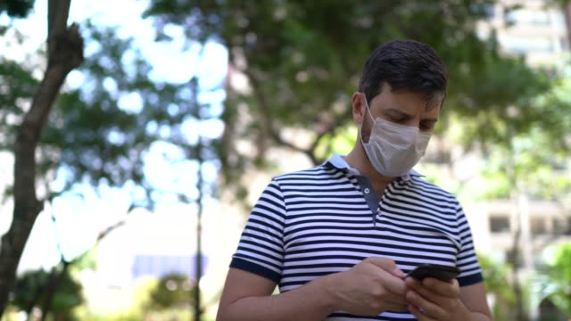 man walking at park using mobile phone - wearing face mask - mobile app stock videos & royalty-free footage
