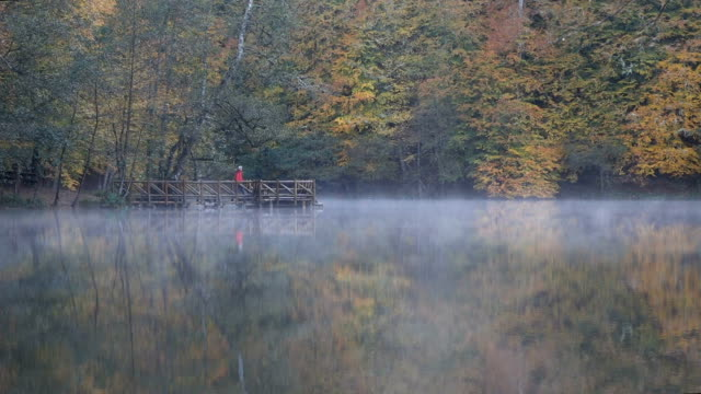 man walking at the pier on foggy lake