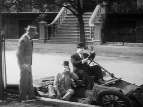 B/W 1931 man walking away from Stan Laurel Oliver Hardy sitting in collapsed car / feature