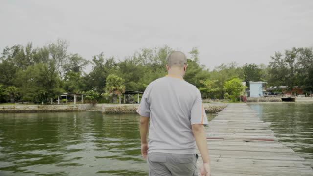木製の橋桟橋に戻って歩く、人 - アノニマス点の映像素材/bロール