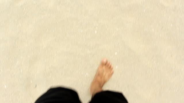 Hombre caminando a pie de playa arenosa expuesto