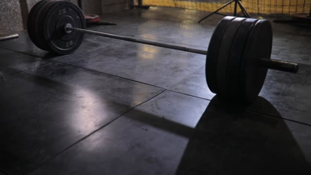 Man walking by barbell with weights in gym
