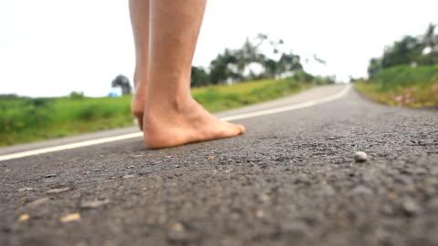 stockvideo's en b-roll-footage met man lopen door barefoot on road - barefoot
