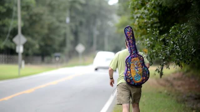 Un homme marche près de l'autoroute avec guitare