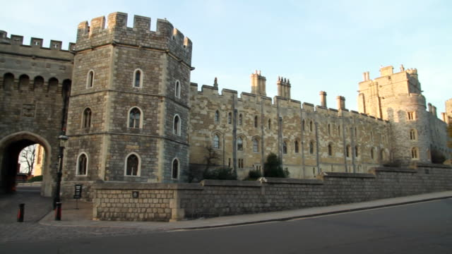 ms pan man walking by large castle street side / windsor, england, united kingdo - windsor castle stock videos and b-roll footage