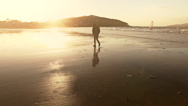 man walking by the sea at sunset - galicia stock videos & royalty-free footage