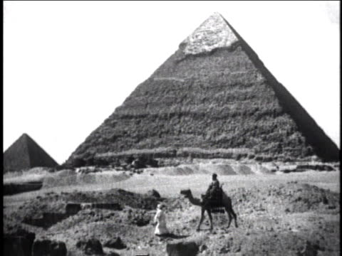 1930 ws man walking camel in front of pyramid / africa - 1930 stock-videos und b-roll-filmmaterial