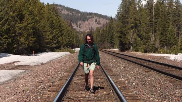 vídeos y material grabado en eventos de stock de hombre caminando directamente hacia la cámara en las vías del tren en el estado de washington - área silvestre