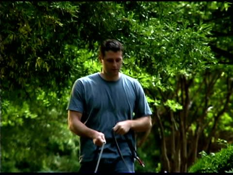 vidéos et rushes de man walking dogs on sidewalk - un seul homme d'âge moyen