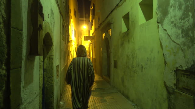 Man walking down a narrow alley in Essaouira