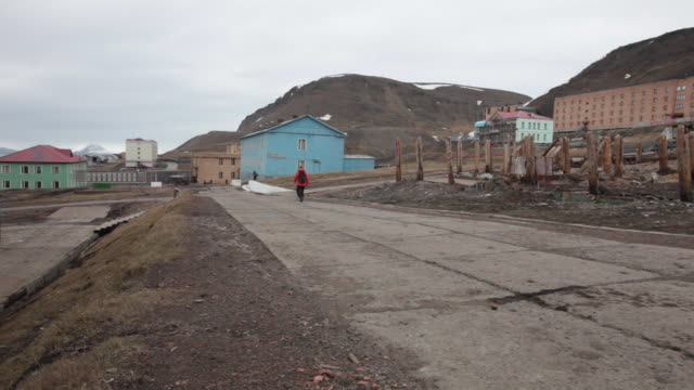 a man walking down a street in barentsburg, a russian mining settlement on svalbard archipelago; some buildings are visible in the back - 1932 stock videos & royalty-free footage