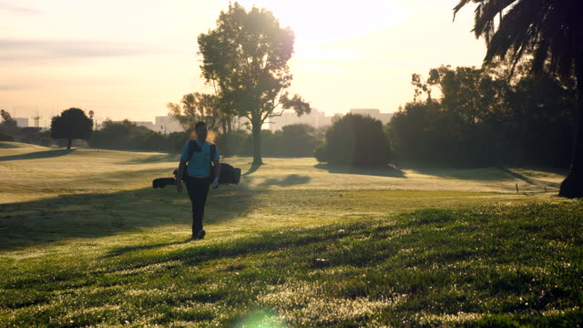 vidéos et rushes de ws man walking down fairway during early morning round of golf - golfeur