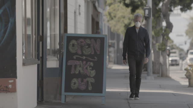 man walking down sidewalk with face mask - lokal stock-videos und b-roll-filmmaterial