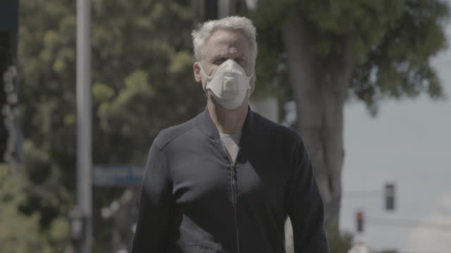 man walking down sidewalk with face mask - driveway stock videos & royalty-free footage