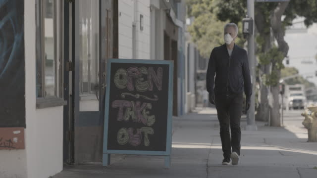man walking down sidewalk with face mask - fast food stock videos & royalty-free footage