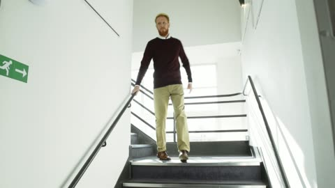 man walking down stairs in office - staircase stock videos & royalty-free footage