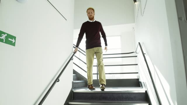 vídeos de stock e filmes b-roll de man walking down stairs in office - degraus