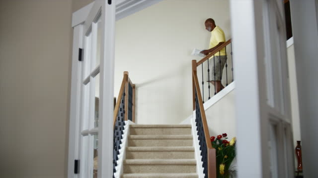 MS Man walking down stairs with coffee and newspaper / Bothell, Washington State, USA