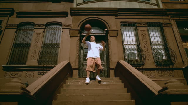 la ws man walking down steps of brownstone, tossing basketball around and doing various tricks/ harlem, new york - front stoop stock videos and b-roll footage