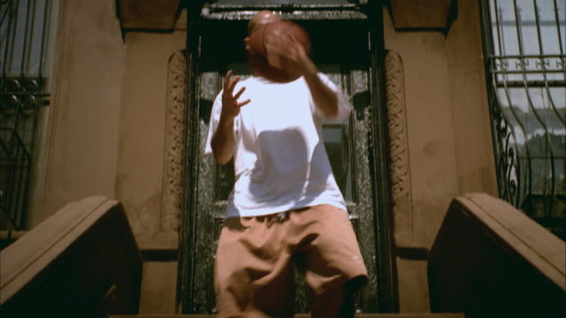 MS TU Man walking down steps of brownstone, tossing basketball around and doing various tricks/ Harlem, New York