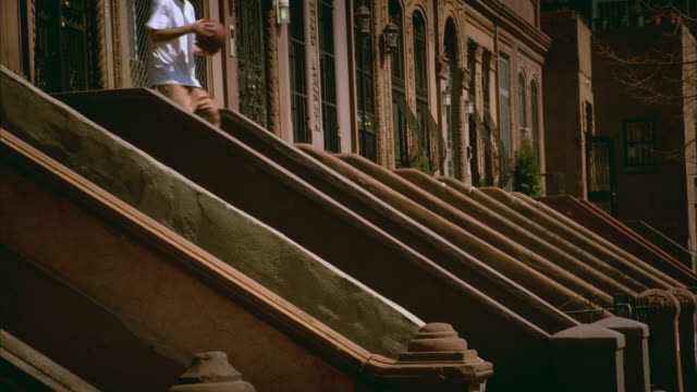 ws man walking down steps of brownstone, tossing basketball around and doing various tricks/ harlem, new york - front stoop stock videos and b-roll footage